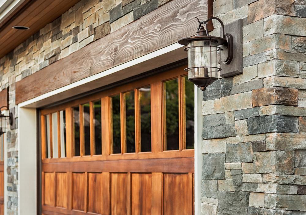 Stilvolle Garage mit Holztor und Natursteinverkleidung